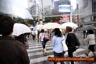 orang jepang memakai payung disaat hujan