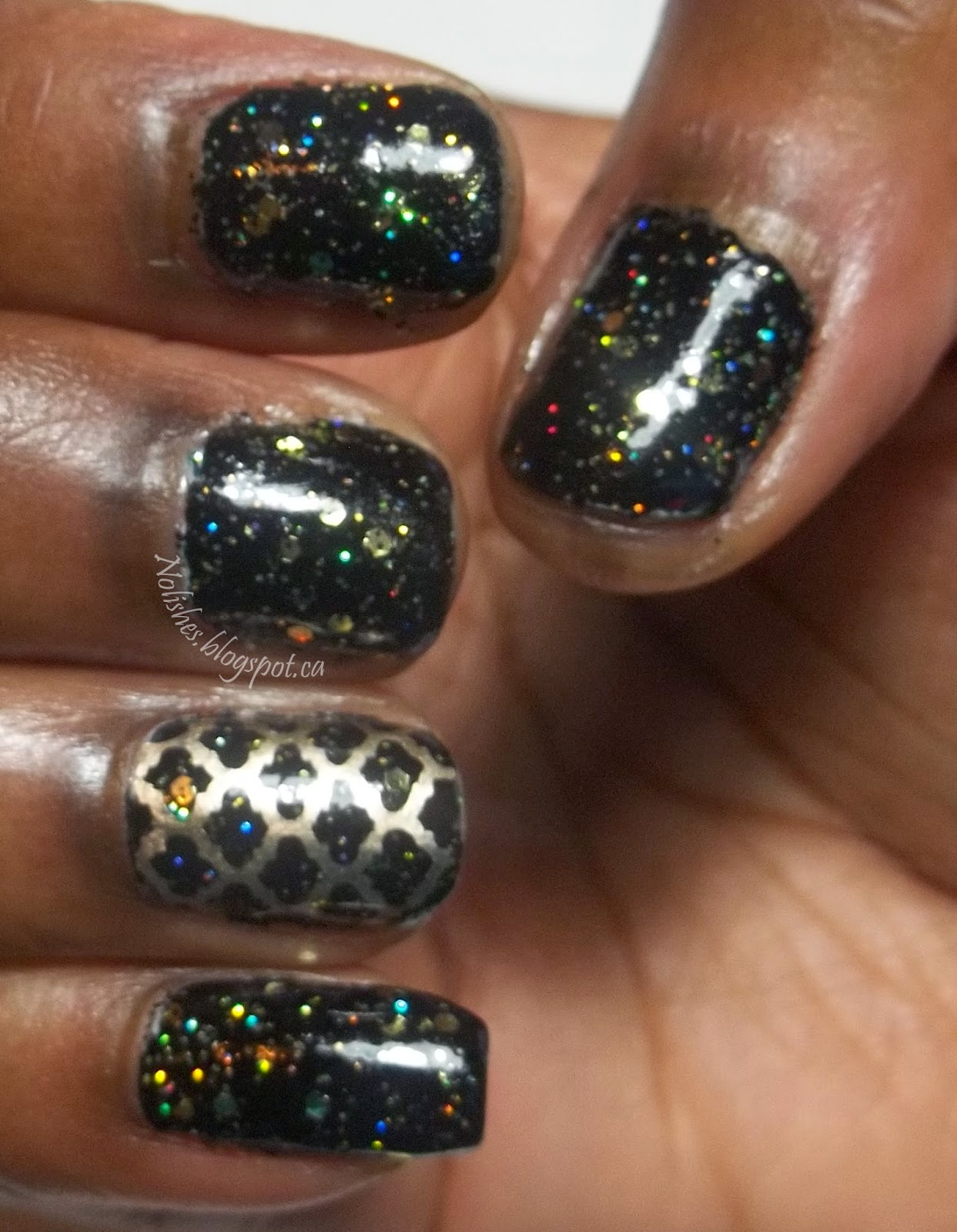 Glitter Manicure featuring black polish, covered with a gold and holographic glitter mix, and a nail stamped quatrefoil lattice pattern stamped in gold on the ring finger.