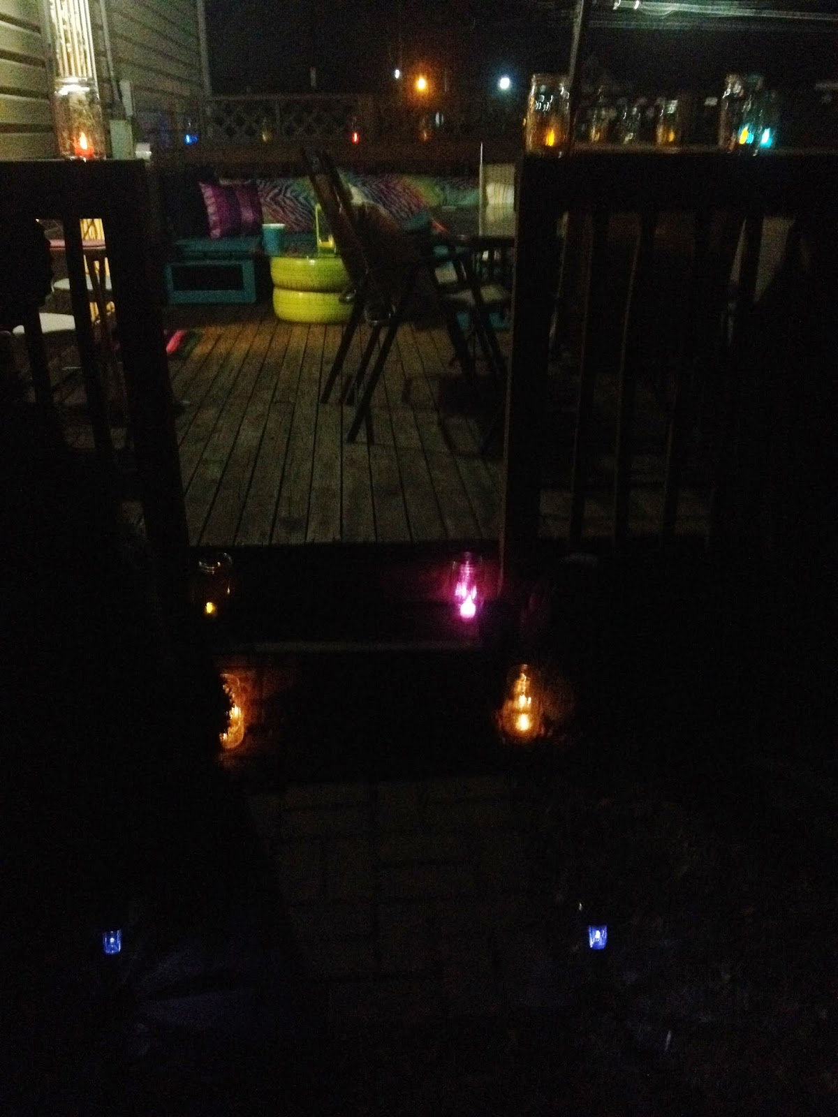 Colorful DIY outdoor deck seating benches makeover with tire table at night
