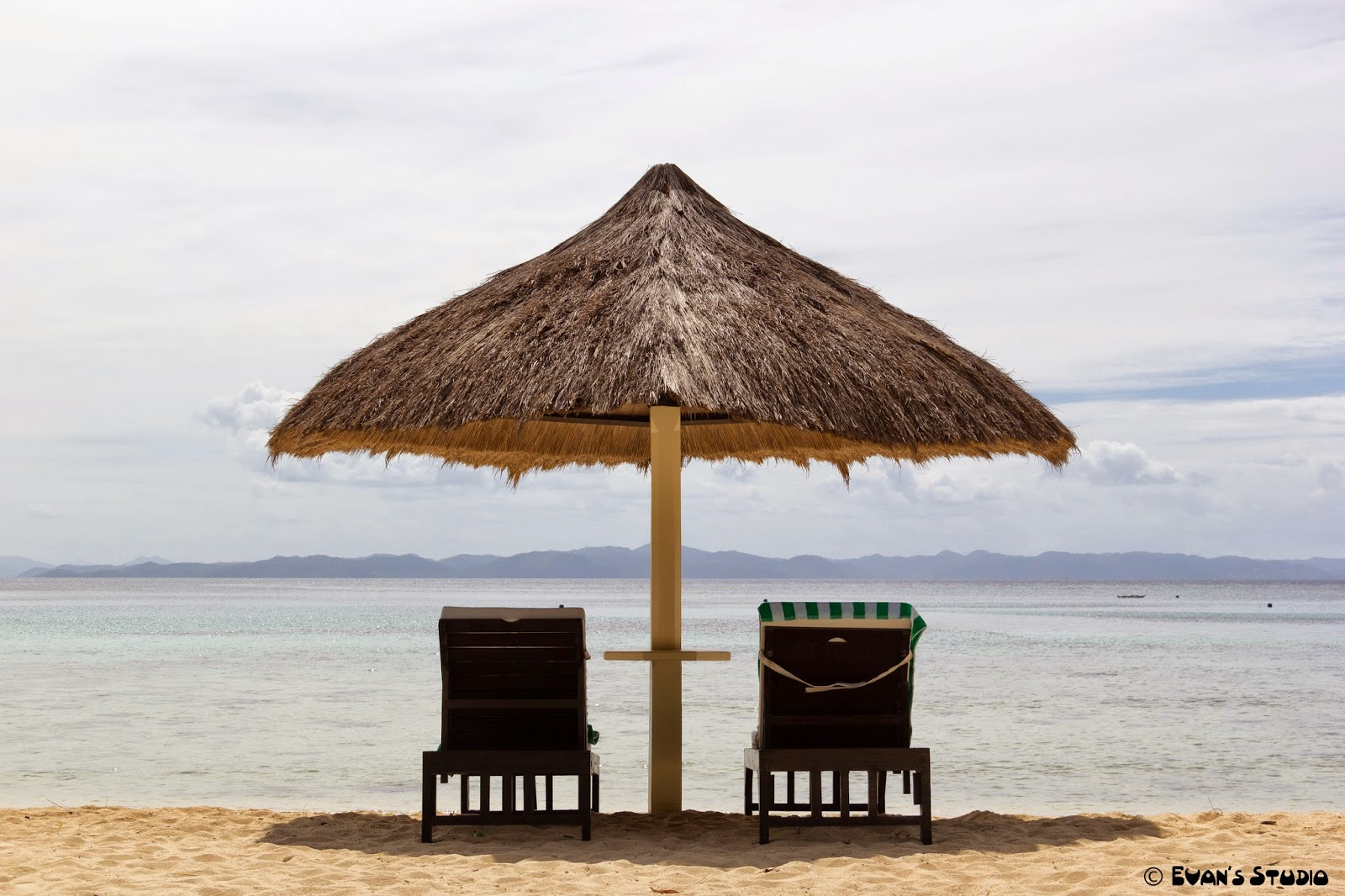 Seats for two on the beach at Apulit Island Resort, in the Philippines.