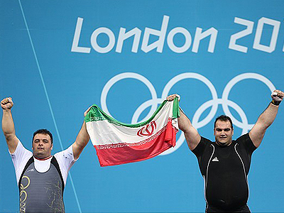 Behdad Salimi and Sajjad Anoushiravani celebrate winning gold and silver respectively at the end of their men's +105kg Group A weightlifting competition during the London 2012 Olympic Games