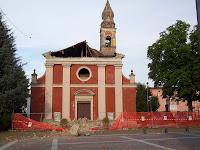 Foto che raffigura la chiesa di Camposanto (MO) col tetto distrutto e recintata dopo il terremoto in Emilia Romagna