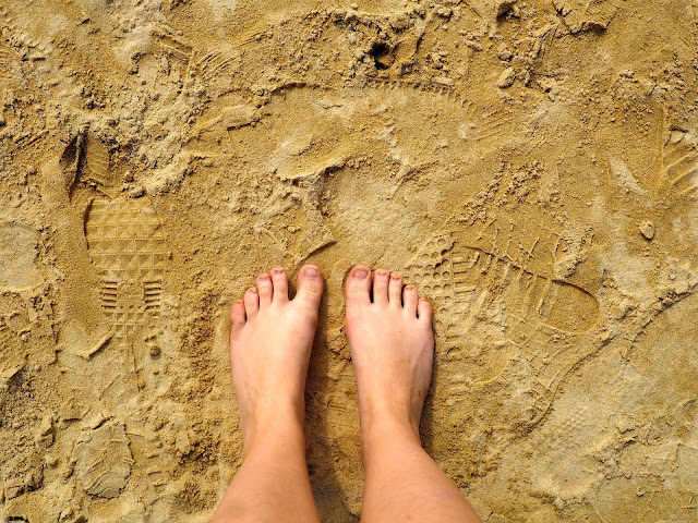 Bare feet in the sand, covered in footprints, on Repulse Bay Beach, Hong Kong