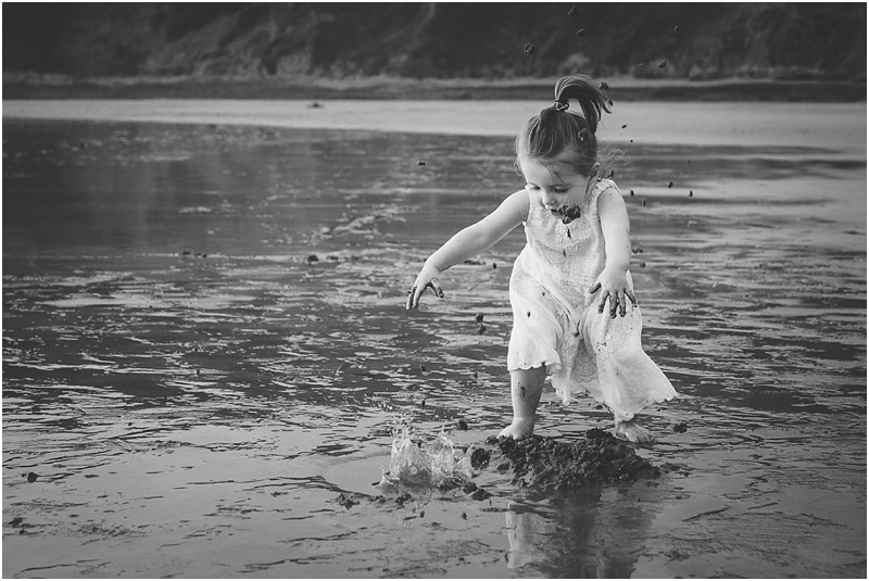 A toddler throwing sand