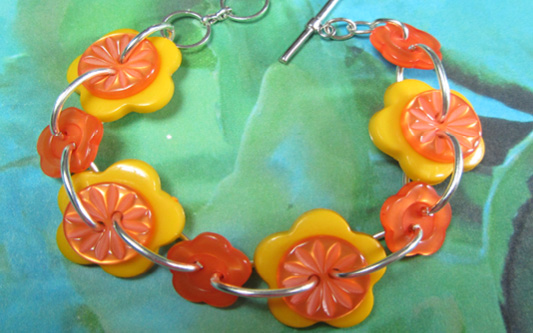 Yellow and orange bracelet has big buttons and flower buttons linked together