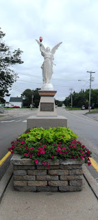 Angel was created by an unknown Quebec artist and placed at the intersection of Acadie Rd and Robichaud St, in Cap-Pelé.