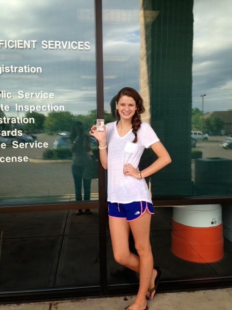 Girl standing in front of license branch with her temporary license.