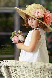 Foto gambar bayi perempuan dengan gaya busana feminim memakai topi cantik