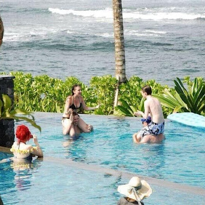 A shirtless Greyson Chance playing chicken in the pool in Bali