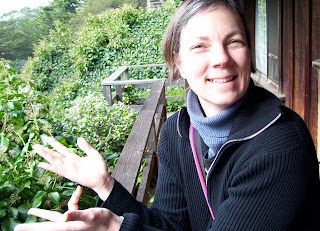Lunden standing outside on a wooden porch at the same height as the treetops which are all around her. She's smiling very widely and holding out her hands with her fingers spread.