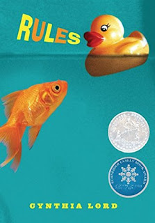 Book cover: Rules by Cynthia Lord. A fish swims upward in water toward a rubber duck that is floating on the water's surface. Circular medalions on the book's cover proclaim it a Newbery Award Honor Book and a Schneider Family Book Award winner.