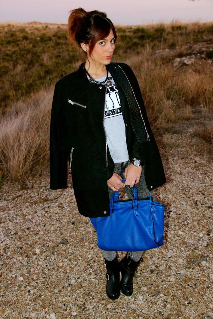 abrigo negro cremalleras, camiseta mensaje, coleta, reloj