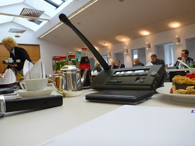 POV Dolmetscherin: Konferenzsaal, Gäste, Servicepersonal und zwei Mikrofone