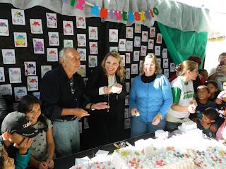 O neto do patrono da escola, parte o bolo comemorativo dos 60 anos do colégio com a diretora Claudia Helena