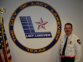 Chief Dennis Stapleton in front of a Lacy Lakeview Fire Department logo.