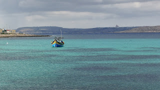 A Luzzu fishing boat in a blue, blue sea