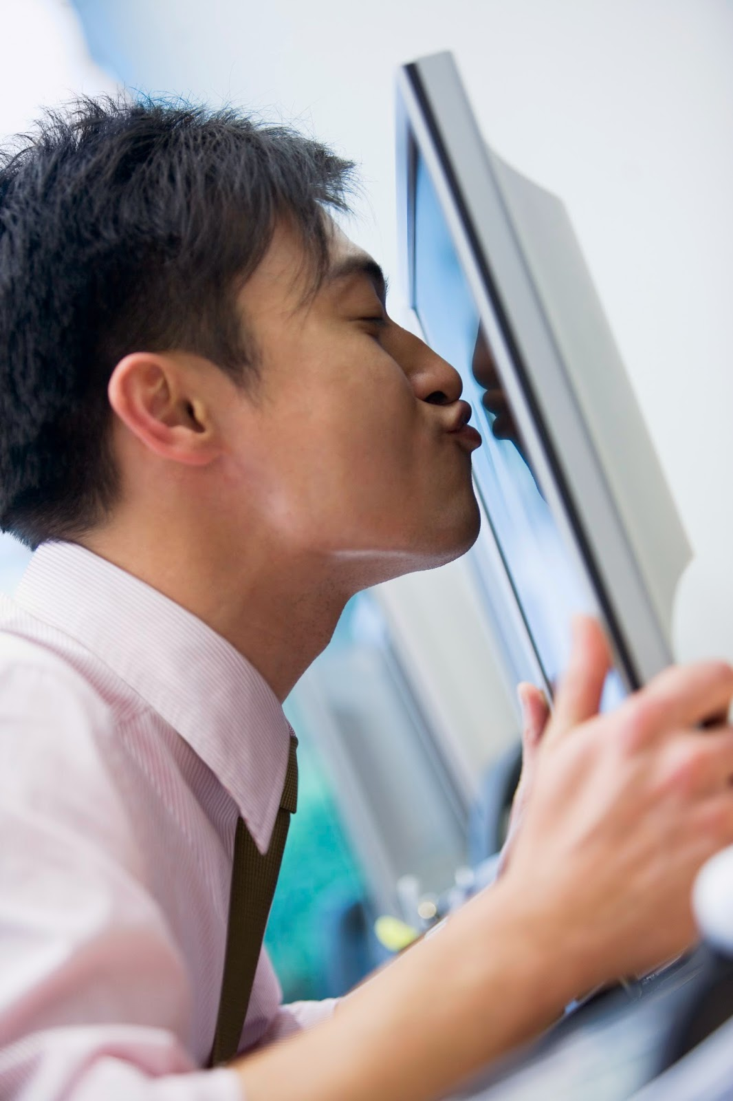 Businessman kissing computer monitor