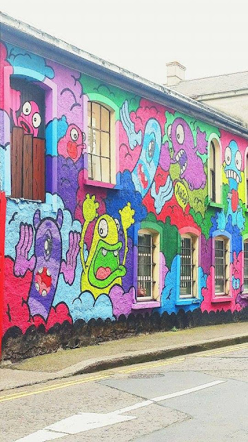 A brightly colored wall with graffiti