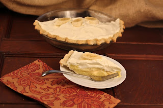 slice of banana cream pie on a plate with red napkin