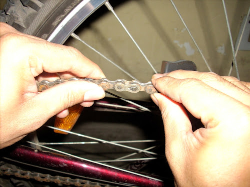 Bicycle chain in two hands with the quick link in the middle