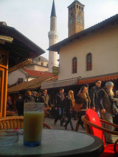 Glass of boza on a table in the old town in Sarajevo with people passing by.