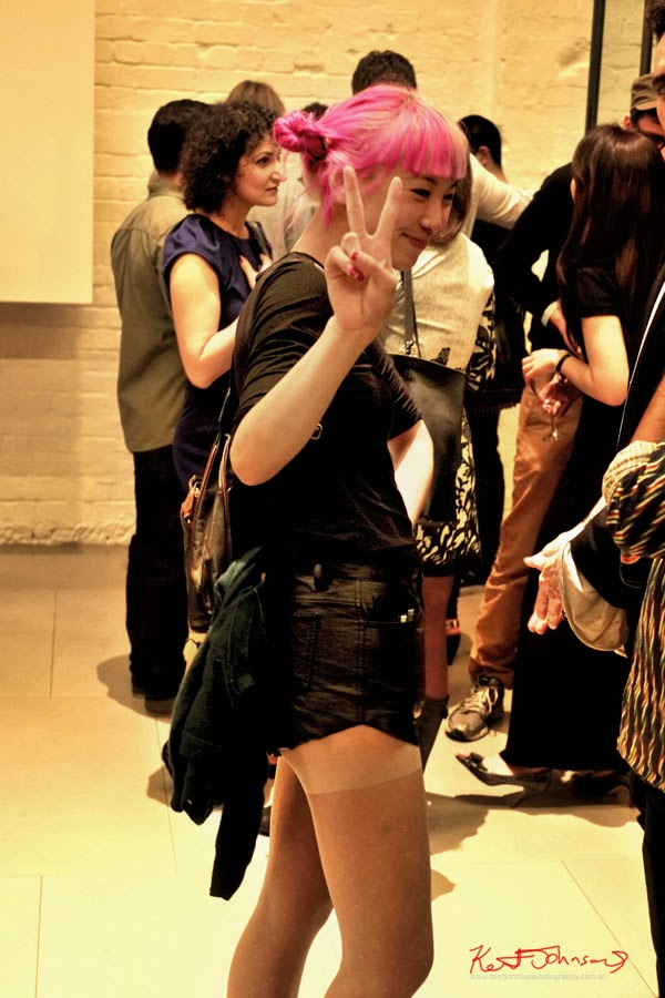 Asian girl with pink hair and nose piercing - short shots inn black with black tee and bag with jacket; at Serve the People art opening at White Rabbit Gallery.