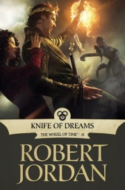 Cover of Knife of Dreams, featuring a young white man raising his arm to protect a young white woman from a burst of flame.