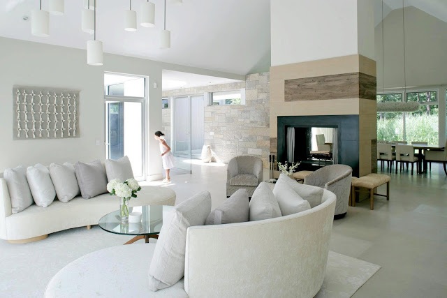 Living room in a white, modern farmhouse with a fireplace, dueling white sofas and white pendant lights