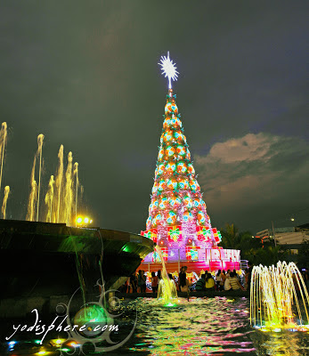 Giant Christmas Tree and colorful water fountain against the dark sky at SM Mall of Asia