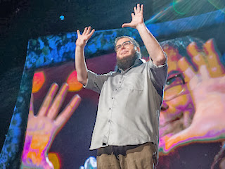 picture of Shane Koyczan holding up his hands