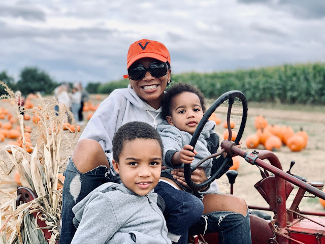 Mom on tractor at pumpkin patch with kids.