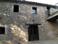 La porta amb brancals de pedra a la façana principal del Molí de Perenoguera