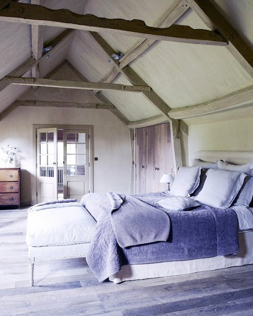 country chic bedroom with reclaimed wood floor, high ceiling, visible beams, and a simple rustic chest of drawers