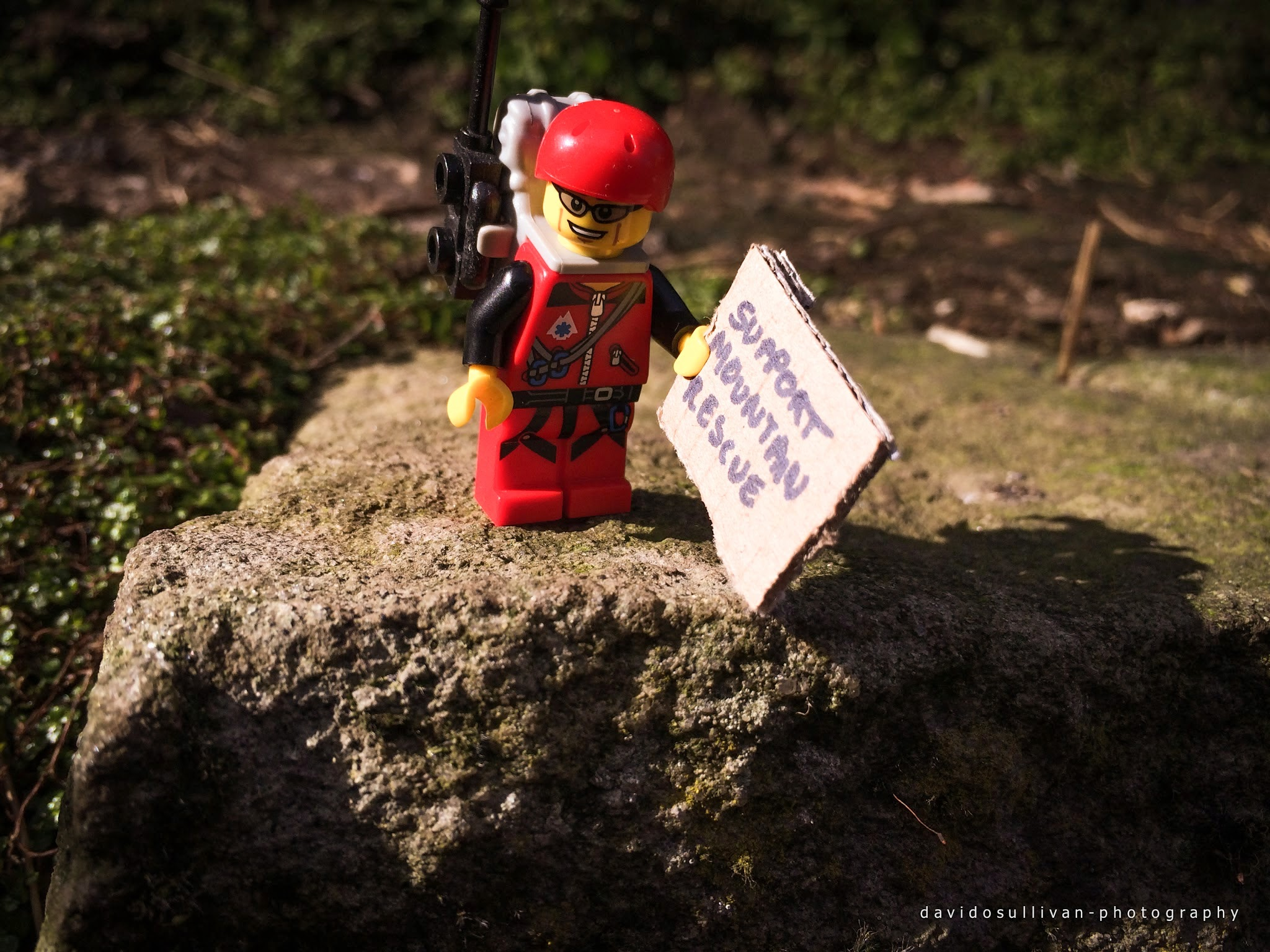 Lego man standing on a rock with a support mountain rescue sign