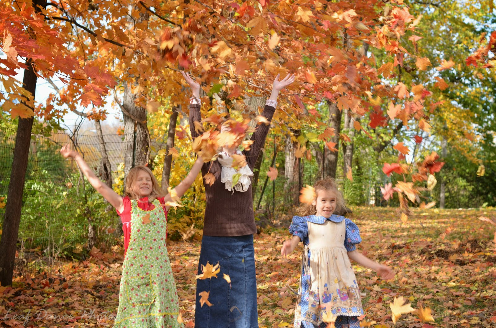 Three Girls throwing leaves into the air