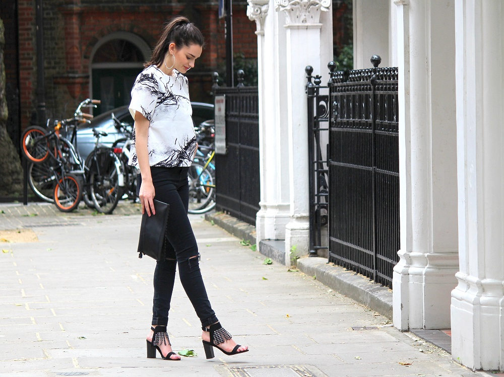 peexo fashion blogger wearing ink print top and ripped black jeans and clutch and fringe heels