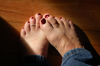 my male painted toes with a toe ring, red polish and jeans, men
