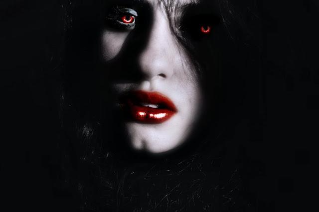 Imagen oscura del rostro de una hermosa vampiro, con los labios rojos al igual que sus ojos.