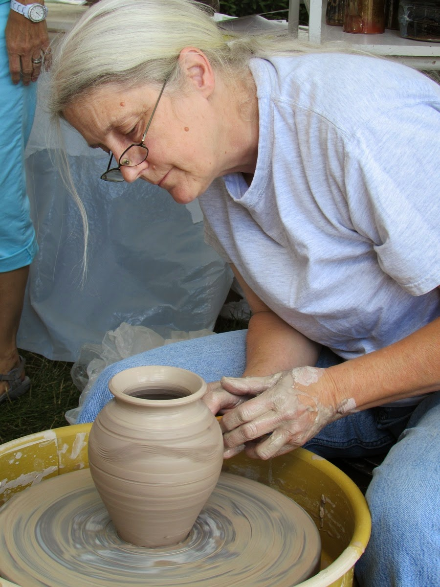 Woman on a potting wheel making a vase