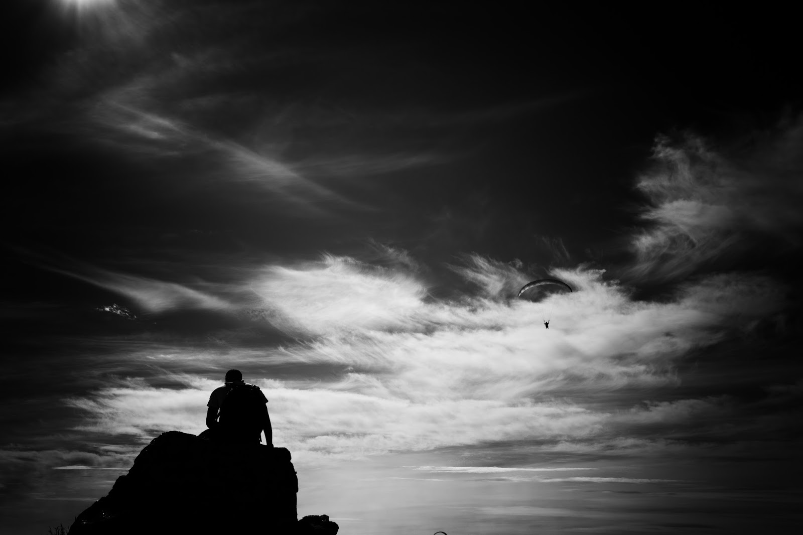 A man sits on a rock silhouetted against a sky while a paraglider flies