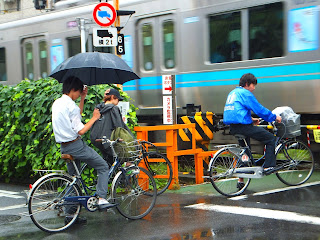 bicycle commuters wait in the rain for a commuter train to pass in Tokyo Japan