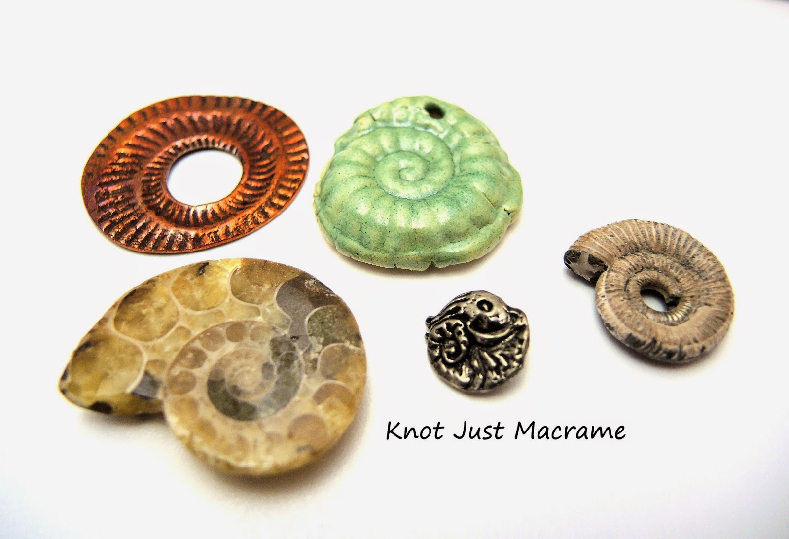 Various ammonites in copper, pewter, ceramic and fossil