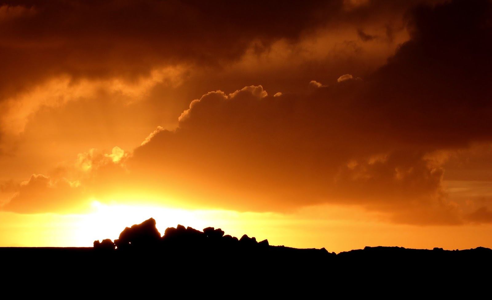 Golden sunset behind black silhouettes of quarry rocks after rain