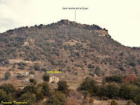 """Vista de conjunt del Serrat de Sant Isidre amb la capella homònima al seu cim i la masia de La Baumeta als seus peus. Autor: Francesc """"Caminaire"""""""