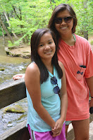 my sister and I standing on a bridge with a river and trees in the background