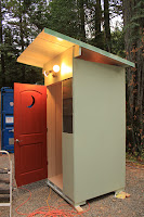 mill creek compost toilet with open roode door and crescent moon cutout