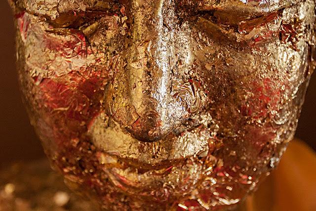 Głowa Buddy z płatkami złota
