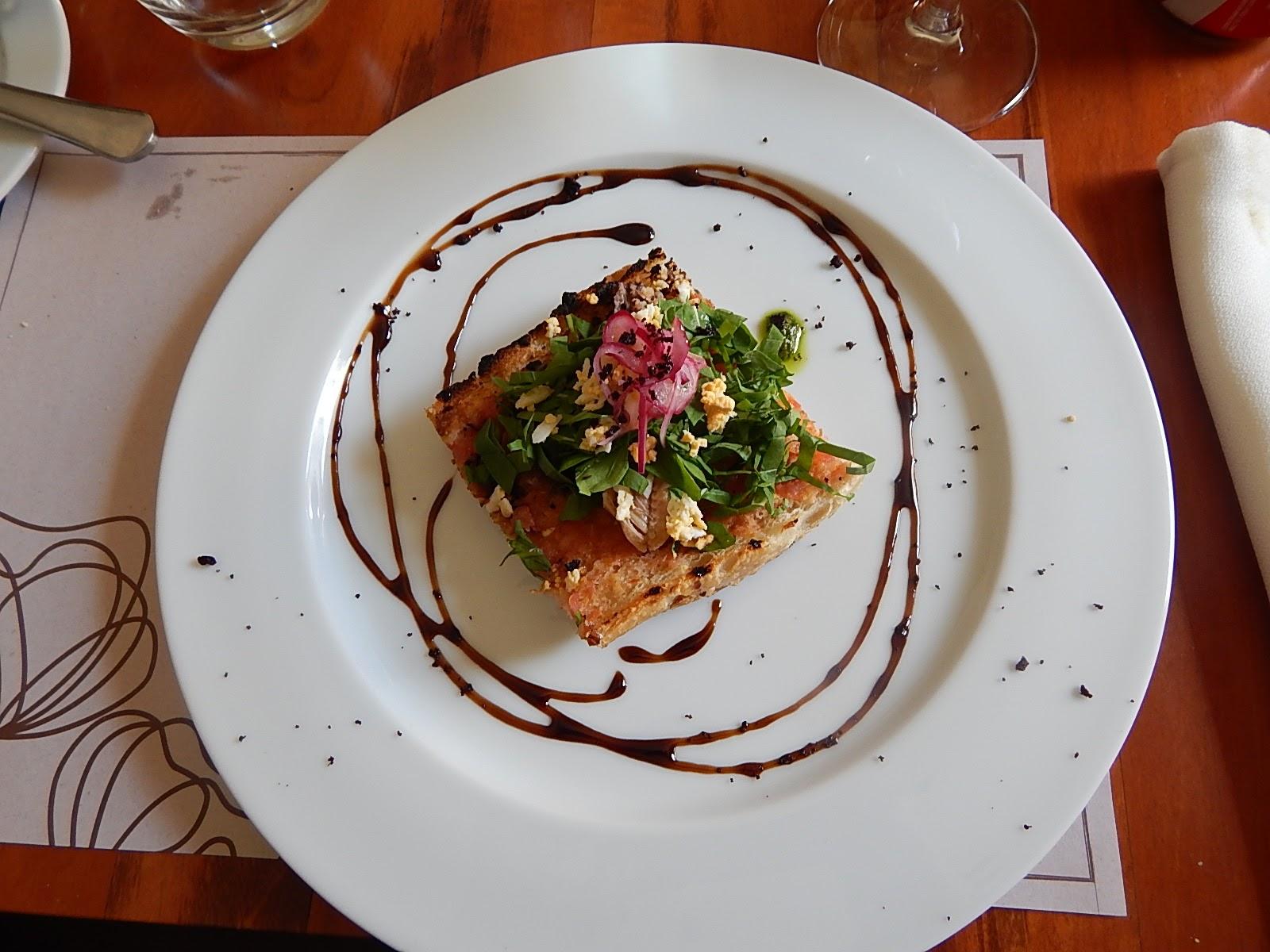 Bruscheta de sardinha com rúcula, ovo cozido, cebola roxa marinada, pesto e azeitonas pretas.