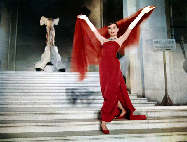 "Audrey Hepburn posing in front of ""Winged Victory at Samothrace"" in the Louvre, Still from Funny Face, 1957"
