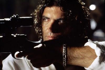 Antonio Banderas apuntando con un rifle de francotirador.
